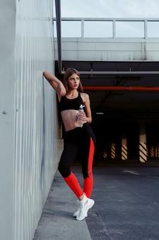 회색 벽 옆에 서 있는 동안 여성 운동선수가 물을 마시고 있습니다. 운동 후 휴식을 취하는 운동복을 입은 날씬한 여성.