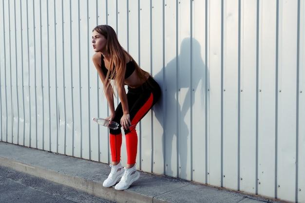 회색 벽 옆에 서 있는 동안 여성 운동선수가 물을 마시고 있습니다.