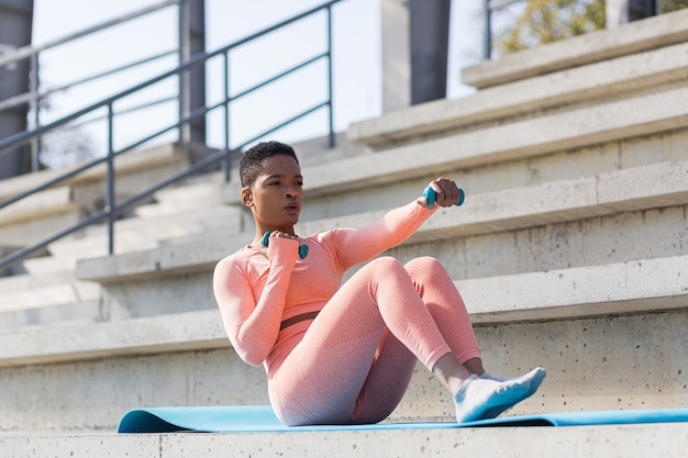 Female athlete exercises with dumbbells near the stadium, african american woman shakes the press and pelvic floor muscles in the morning at the sports stadium