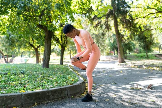 女性アスリートは朝のジョギングとフィットネスの後に重度の下肢痛の怪我をしています、朝の秋の公園でアフリカ系アメリカ人の女性