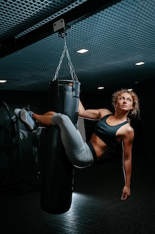 Female athlete is hanging on a punching bag to perform exercises on the press concept of fitness and...