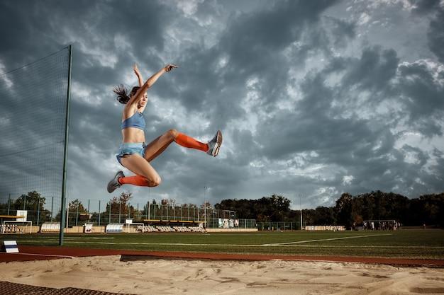 경기장에서 훈련에서 점프 하는 여성 운동 선수. 점프, 운동 선수, 액션, 모션, 스포츠, 성공 및 훈련 개념