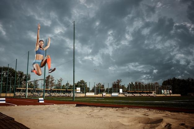 경기장에서 훈련하는 여성 운동선수. 점프, 운동 선수, 액션, 모션, 스포츠, 성공 및 훈련 개념