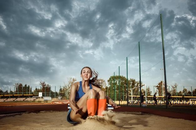 경기장에서 훈련하는 동안 점프하는 여성 운동선수. 점프, 운동 선수, 액션, 모션, 스포츠, 성공, 챔피언십 개념