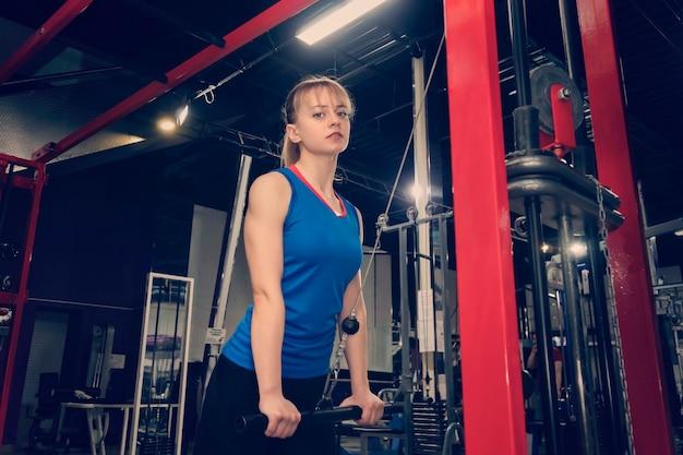 크로스 경쟁에 조정 기계에 여성 선수입니다. 막대를 올립니다. 무게를 들어 올리십시오. 파란색 양복을 입은 선수는 스포츠 시뮬레이터에서 많은 무게를 올립니다. 손 근육 훈련. 섹시한 운동가.