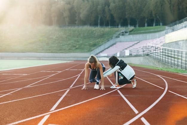 트랙에 있는 여성 운동 선수는 경기장에서 시작하는 개인 트레이너와 함께 운동합니다.