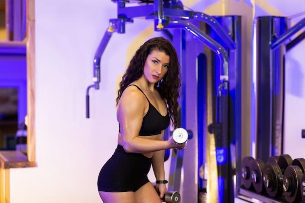 Спортсменка выполняет упражнения с гантелями в тренажерном зале