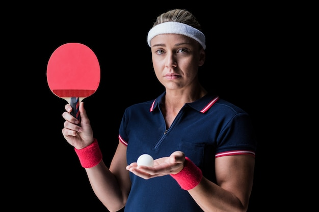 Female athlete playing ping pong on black