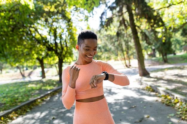 여자 운동선수는 아침에 공원에서 뛰고, 피트니스 팔찌를 보고, 자신의 결과의 성공에 기뻐합니다