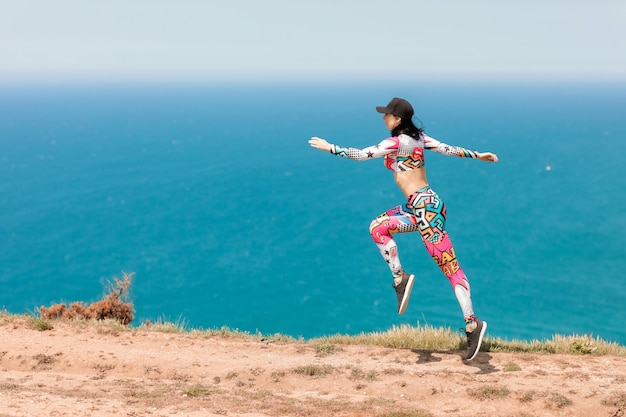Female athlete on the sea coast performs exercises before training and running