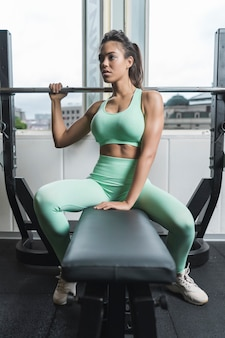 Female athlete sitting on a bench in a gym and looking away. she is wearing green sportswear. she is combing ponytail