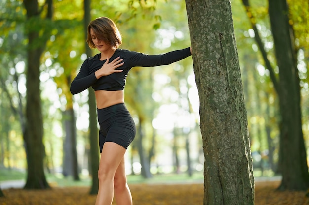Female athlete in sport clothing stretching arms outdoors