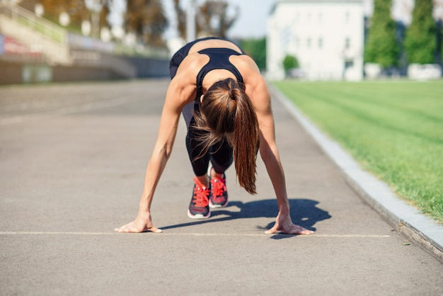 Female athlete on the starting line of a stadium track, preparing for a run