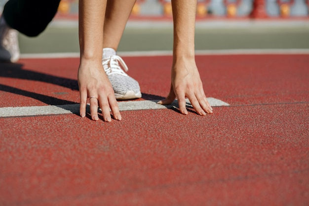 Female athlete at starting position ready for the race. space for text