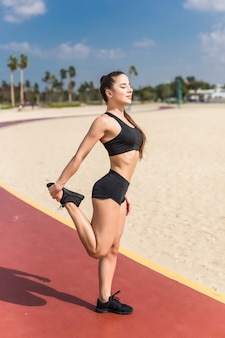 Female athlete stretching before running and exercising at the beach on summer. sporty fitness woman training outdoor.