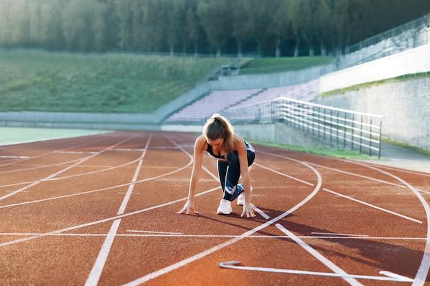 아침 빛 젊은 여성 주자에서 트랙에서 훈련하는 여성 운동 선수