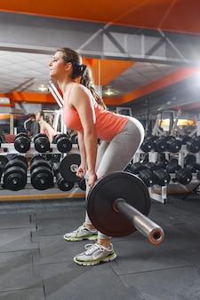 Спортсменка тренируется в тренажерном зале со штангой