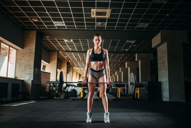 スポーツジムでバーベルを使ってトレーニングする女性アスリート
