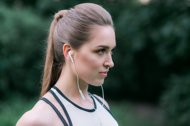 Female athlete wearing earphones. woman listening to music during workout outdoor.