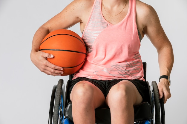 Female athlete in a wheelchair holding a basketball