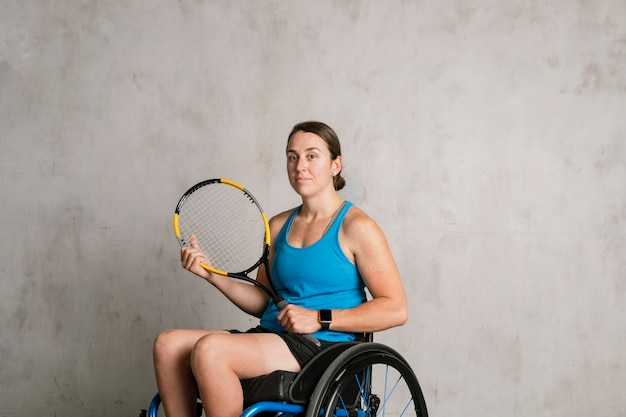 Female athlete in a wheelchair holding a tennis racket