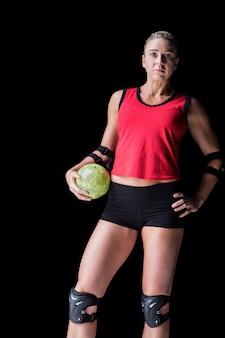 Female athlete with elbow pad holding handball on black
