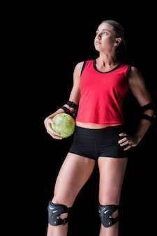 Female athlete with elbow pad holding handball on black