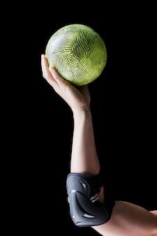 Спортсменка с налокотник держит гандбол на черном