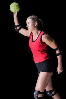 Female athlete with elbow pad throwing handball on black