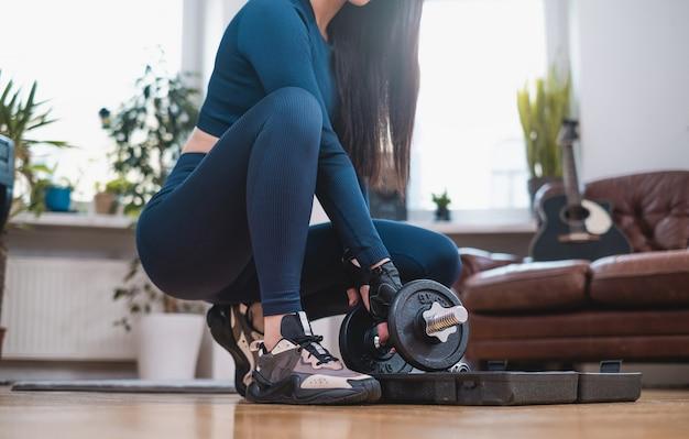 Спортсменка с стройной фигурой готовит спортивный инвентарь для тренировки в гостиной с современной мебелью.