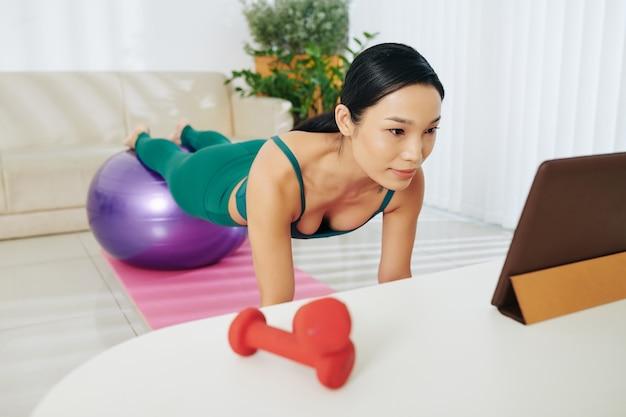 Спортсменка работает дома, делая упражнения планка с ногами на фитнес-мяче