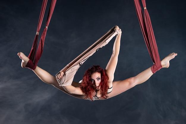 빨간 머리가 실크 위에서 춤을 추는 여성 운동, 섹시하고 유연한 공중 서커스 아티스트.