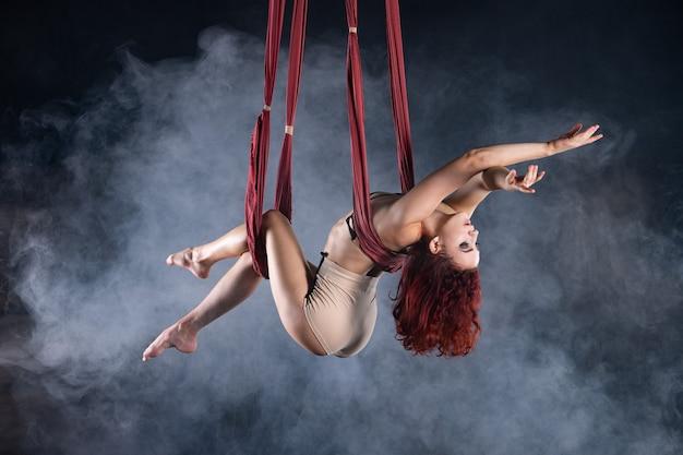 Атлетичная, сексуальная и гибкая артистка воздушного цирка с рыжей танцует в воздухе на шелке.