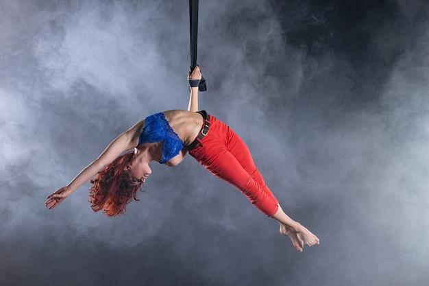 검은 색 바탕에 공중 끈에 빨간 머리를 가진 여성 운동, 섹시하고 유연한 공중 서커스 아티스트.