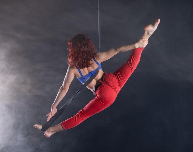 공중 끈에 빨간 머리를 가진 여성 운동, 섹시하고 유연한 공중 서커스 아티스트