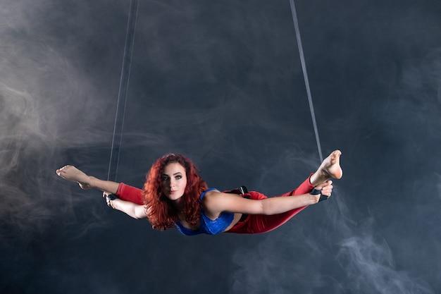 공중 끈에 빨간 머리를 가진 여성 운동, 섹시하고 유연한 공중 서커스 아티스트.