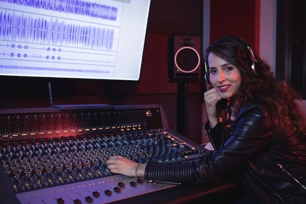 Female audio engineer using sound mixer