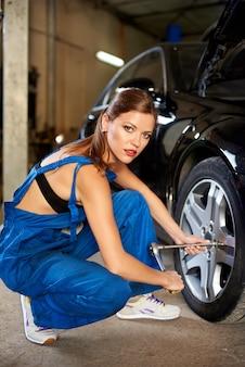 Женский автомеханик ремонтирует машину в гараже