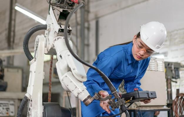Инженер по автоматизации женского пола носит синюю форму с контролем безопасности шлема, сварочный аппарат робота с дистанционной системой на промышленном заводе. концепция искусственного интеллекта.
