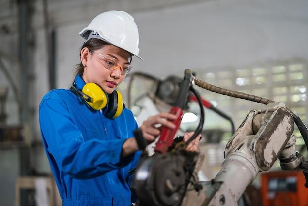 女性の自動化エンジニアは、工業工場のリモートシステムを備えたロボットアーム溶接機を制御するヘルメット安全検査を備えた青いユニフォームを着用しています。人工知能の概念。