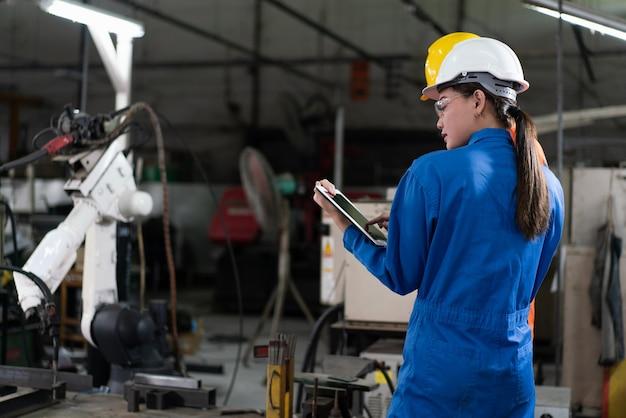女性のオートメーション エンジニアは、ヘルメットの安全検査で青い制服を着て、産業工場でタブレットを使ってロボット アームの溶接機を制御します。人工知能のコンセプト。