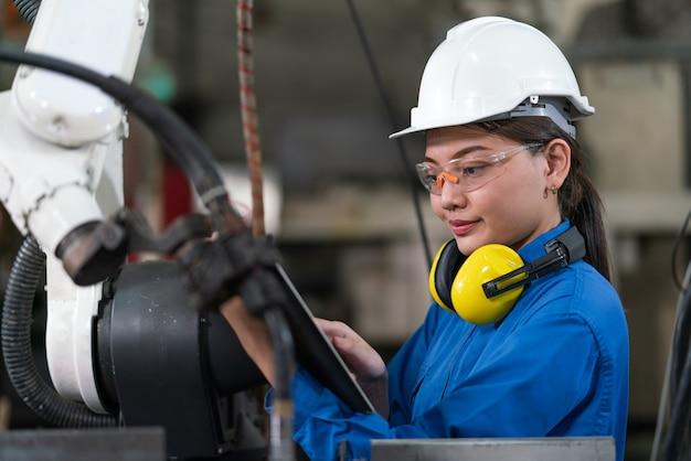 女性の自動化エンジニアは、工業工場でヘルメットの安全検査制御を備えた青いユニフォームを着用し、タブレットを備えたロボットアーム溶接機を制御します。人工知能の概念。