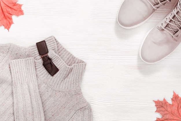女性の秋の服、暖かいウールジャンパー、メープルトレンドカラーの白い木で飾られた紅葉のコンフォートブーツ。上面図。フラット横たわっていた。