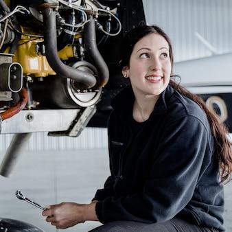 Female aviation technician repairing the motor