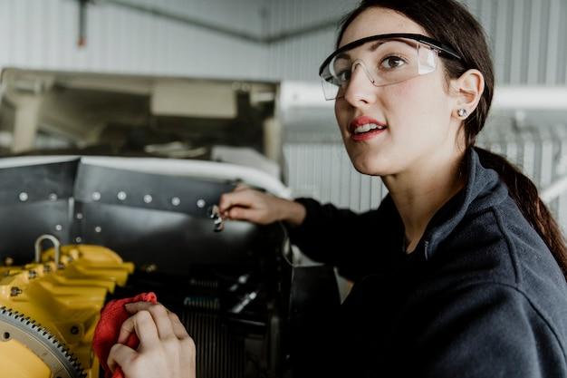 Женский авиационный техник, ремонтирующий двигатель винтового самолета