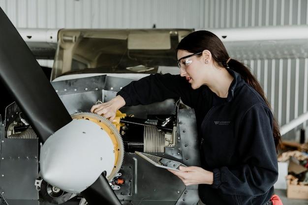 Женский авиационный техник, ремонтирующий двигатель винтового самолета Premium Фотографии