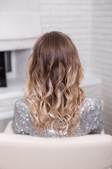 Женская спина со светлыми вьющимися волосами омбре