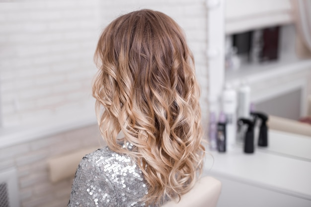 Female back with blonde curly ombre hair