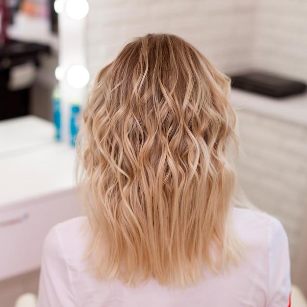 Женская спина с вьющимися светлыми волосами омбре в парикмахерской
