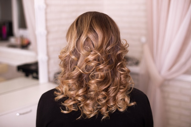 Female back with curly, ombre, brunette hair, in hairdressing salon